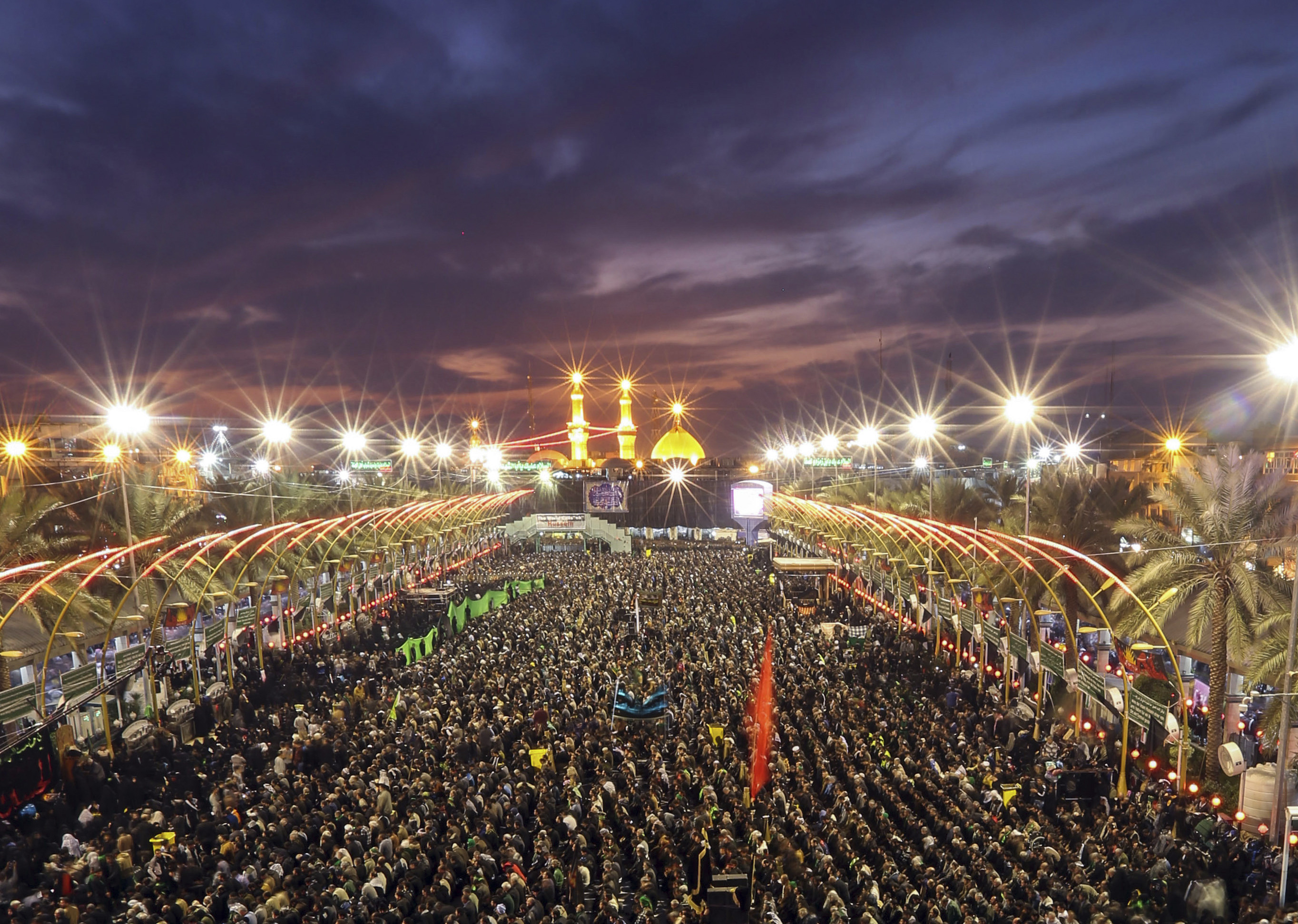Shiite faithful pilgrims gather between the holy shrine of Imam Hussein and the holy shrine of Imam Abbas, in the background, during the preparations for the Muslim festival of Arbaeen in the Shiite holy city of Karbala, 50 miles (80 kilometers) south of Baghdad, Iraq, Friday, Dec. 12, 2014. The holiday marks the end of the 40-day mourning period after the anniversary of the 7th century martyrdom of Imam Hussein, the Prophet Muhammad's grandson. (AP Photo/Hadi Mizban)